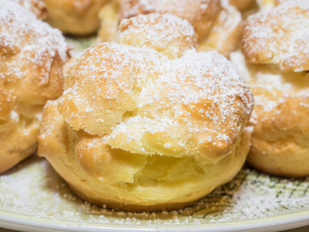 Homemade choux pastry ball filled with whipped cream, pastry cream. Stock Photo
