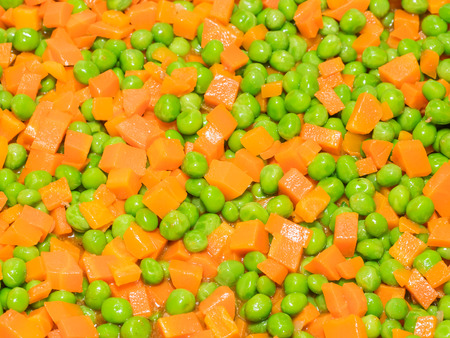 Boiled carrots mixed with frozen sweet peas. photo