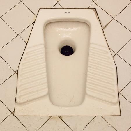 Baño en cuclillas consiste en un agujero en el suelo. Para utilizar este sanitario, uno se encuentra en una posición en cuclillas en lugar de sentarse, colocando un pie a cada lado de la taza del baño y en cuclillas sobre él. Foto de archivo - 28142231
