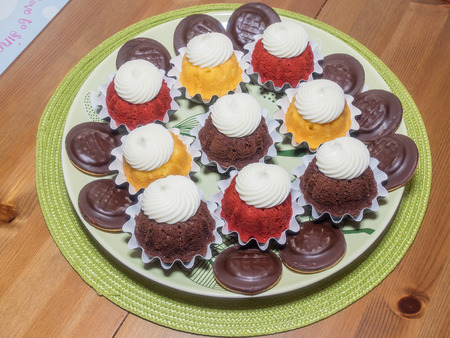 Plate full of delicious home made cupcakes with cream.