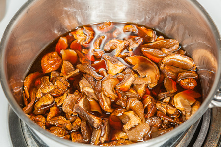 soaking: Dried mushrooms soaking in water in preparation for Christmas cooking. Stock Photo