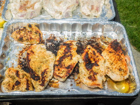 Grilling marinated chicken breasts during picnic in a park.