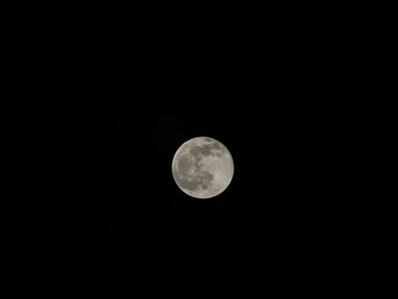 occurs: Full moon is the lunar phase that occurs when the moon is completely illuminated as seen from the earth. Stock Photo