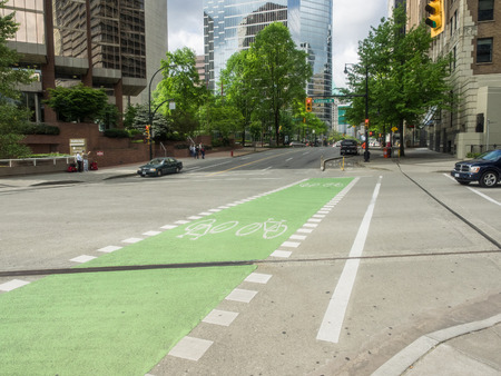 road cycling: Green bike path on a street in Vancouver Downtown.
