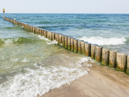 Wooden breakwater structures on the beach in Kolobrzeg, Poland