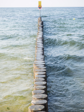 Wooden breakwater structures on the beach in Kolobrzeg, Poland