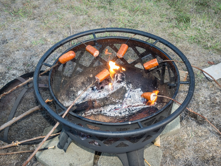 pit fall: Roasting sausages on wooden sticks over a fire pit