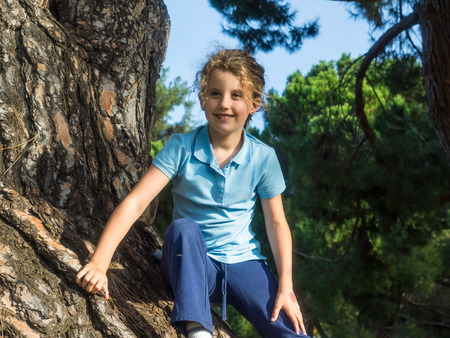 Having fun climbing on a tree in a park on sunny fall day. photo