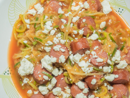 Squash spaghetti noodles with sausage and tomato sauce garnished with feta cheese.