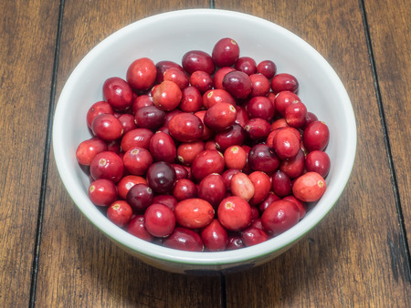 Bowl of fresh organic cranberries on wooden table. photo