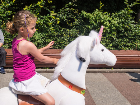 Riding toy ponies on major tourist promenade in Kolobrzeg, Poland Standard-Bild