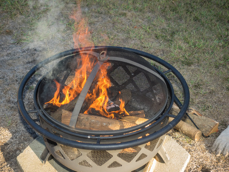 Outdoor metal fire pit with mesh cover on backyard.