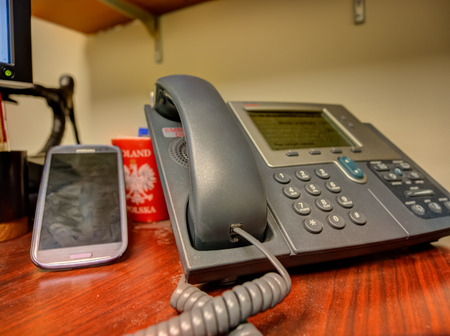 mobile voip: Cell phone next to VoIP phone on a desk in office