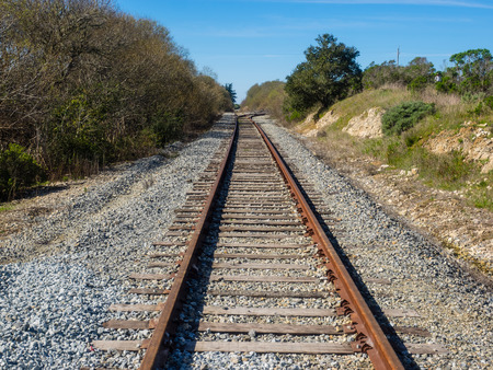 converge: Railroad tracks appear to converge in the distance because we see them with our eyes from ground level