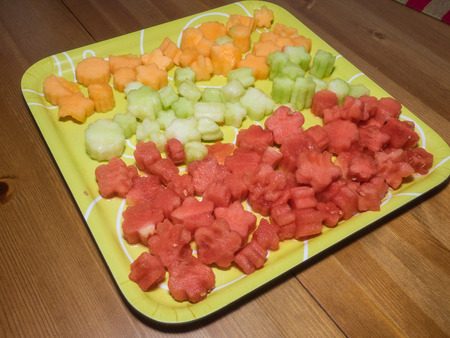 Flowers carved from cantaloupe, honeydew  and watermelon on green square plate. Фото со стока