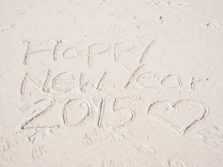 Happy New Year sign written on white desert sand. photo