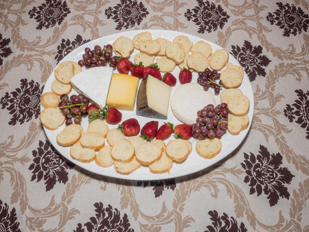 Large platter with assorted cheeses, fruits and bread on party table.