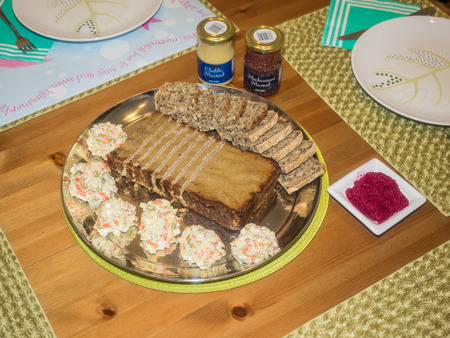 Plate with pate, vegetable salad and bread in a center of Easter dinner table.