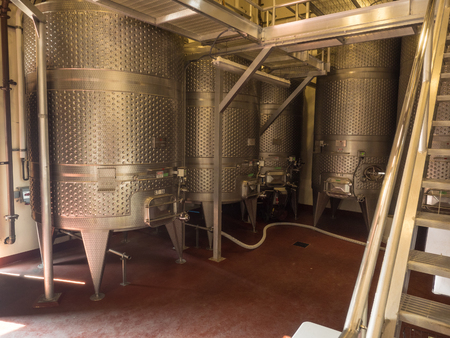 fermentation: Metal wine fermentation containers in vineyard.