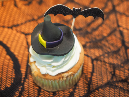white cream: Spooky Halloween cupcakes with white cream and decorations on top.