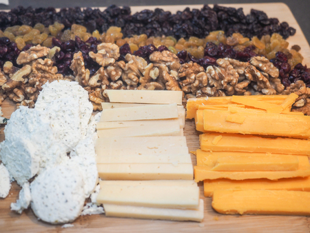 Assorted cheeses and nuts served on wooden cutting board. Imagens
