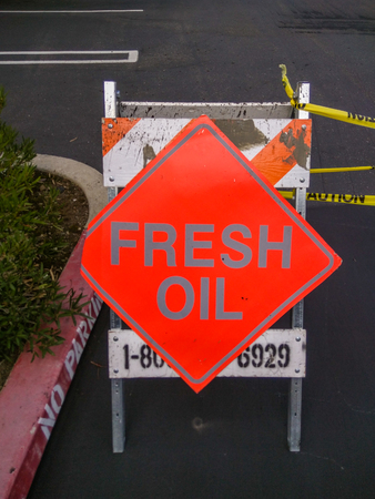 pavers: Fresh Oil sign usually refers to the tack pavers use before laying the asphalt. Stock Photo