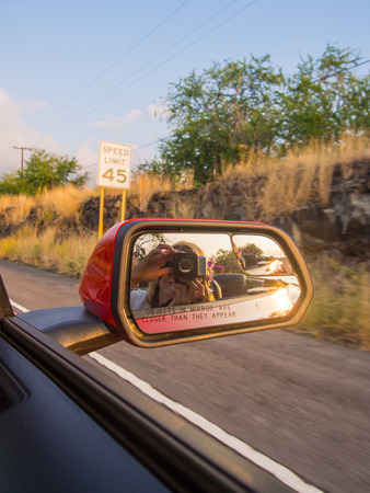 Looking back at the road view in side mirror while driving. Imagens