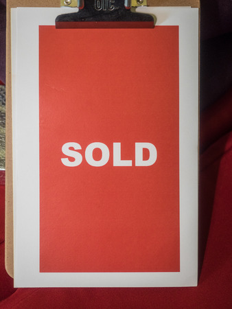 sold sign: Clipboard holding red sold sign during auction Stock Photo