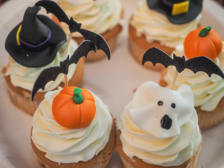Spooky Halloween cupcakes with white cream and decorations on top.
