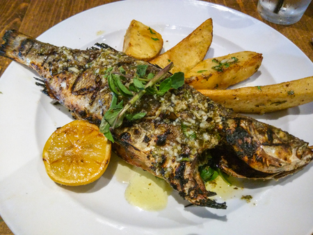 lemon wedge: Whole grilled Mediterranean sea bass with sauteed spinach and lemon wedge potatoes