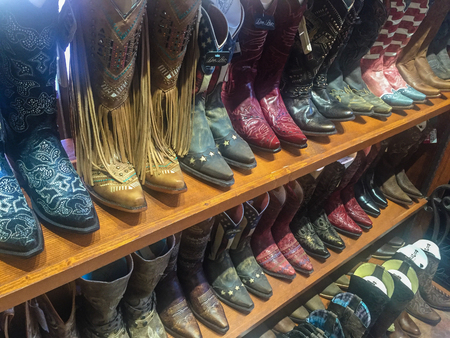 store shelf: Rows of cowboy boots on shelf in store in Dallas, Texas
