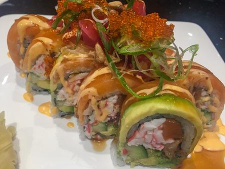 Sushi Roll contains crab, unagi, avocado, salmon, tuna, cucumber topped with salmon, avocado, spicy tuna, tobiko, pine nuts.