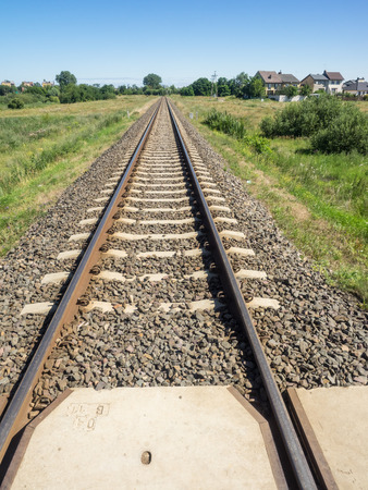 converge: Railroad tracks appear to converge in the distance because we see them with our eyes from ground level.
