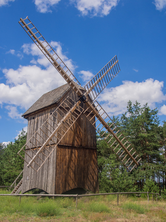 smock: Smock mill is a type of windmill that consists of a sloping, horizontally weatherboarded or thatched tower, usually with six or eight sides. Stock Photo