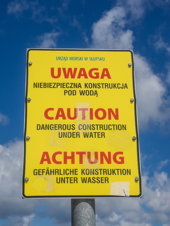 Yellow warning sign about breakwaters in water on Baltic sea coast in Poland
