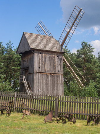 Smock mill is a type of windmill that consists of a sloping, horizontally weatherboarded or thatched tower, usually with six or eight sides. Stock Photo