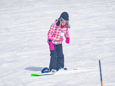 Beginner kids snowboarding lesson is the fastest way to learn skills and safety. Stock Photo