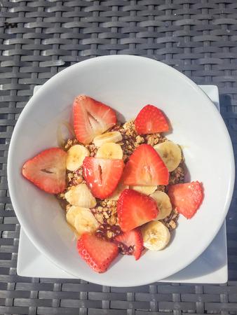 Fruit bowl containing bananas mixed with berries, yogurt and granola.
