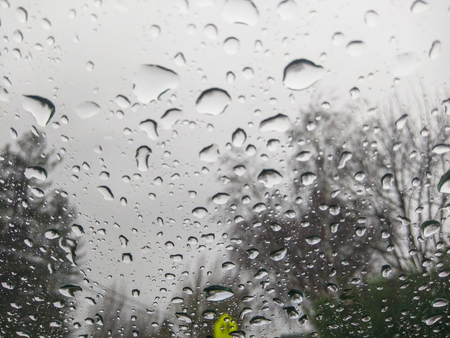 Raindrops on windshield with blurry view behind.