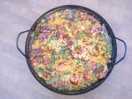 Paella is a Valencian rice dish consists of white rice, green beans, meat, white beans, snails, and seasoning such as saffron and rosemary. Seafood paella replaces meat with seafood and omits beans and green vegetables.
