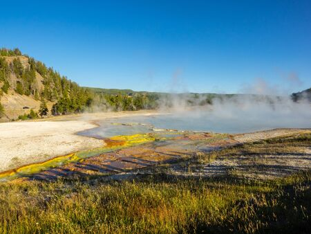 Midway Geyser Basin is much smaller than the other basins found alongside the Firehole River. The largest hot spring in Yellowstone, the 370-foot-wide (110 m) and 121-foot-deep (37 m) Grand Prismatic Spring is also found here. Stok Fotoğraf
