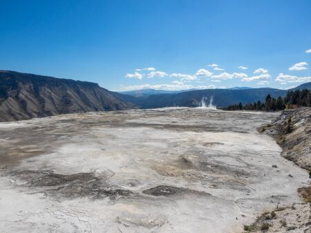 Mammoth Hot Springs is a large complex of hot springs on a hill of travertine in Yellowstone National Park. The hot water that feeds Mammoth comes from Norris Geyser Basin after traveling underground via a fault line that runs through limestone. Reklamní fotografie