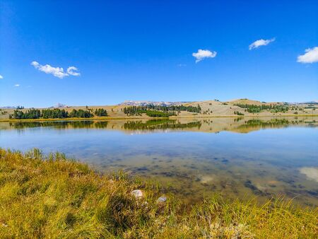 A calm Swan Lake, in the northwest corner of Yellowstone, reflects mountains in the Gallatin Range.