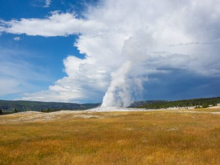 Old Faithful is a cone geyser located in Yellowstone National Park in Wyoming, United States. Stock Photo