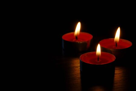 Burning red candles for backgrounds. Many colors candies on a wooden table for background images