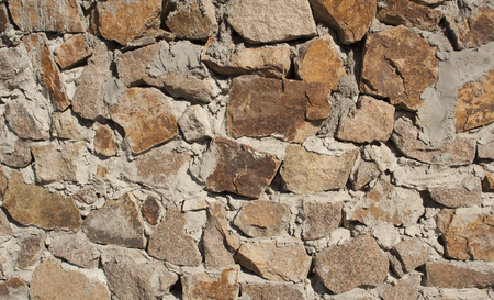 Wall of rough large granite stones of brown color
