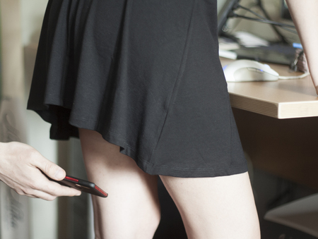 A man photographs a mobile phone under the skirt of a woman. Sexual harassment at work