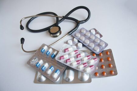 Many different pills and a stethoscope are on the table