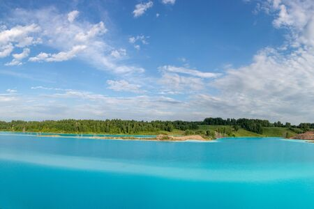 Panorama of a beautiful lake with azure-blue water. Green trees, blue sky with white clouds. Summer sunny day