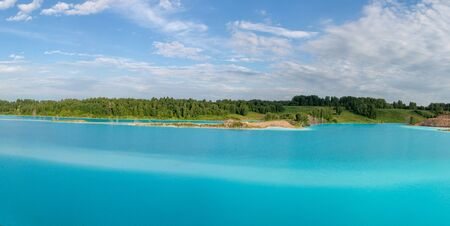 Panorama of a beautiful lake with azure-blue water. Green trees, blue sky with white clouds. Summer, sunny day. Horizontal photo Stok Fotoğraf